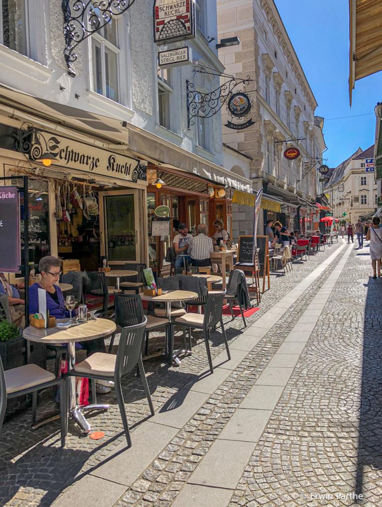Narrow street with outdoor restaurants.
