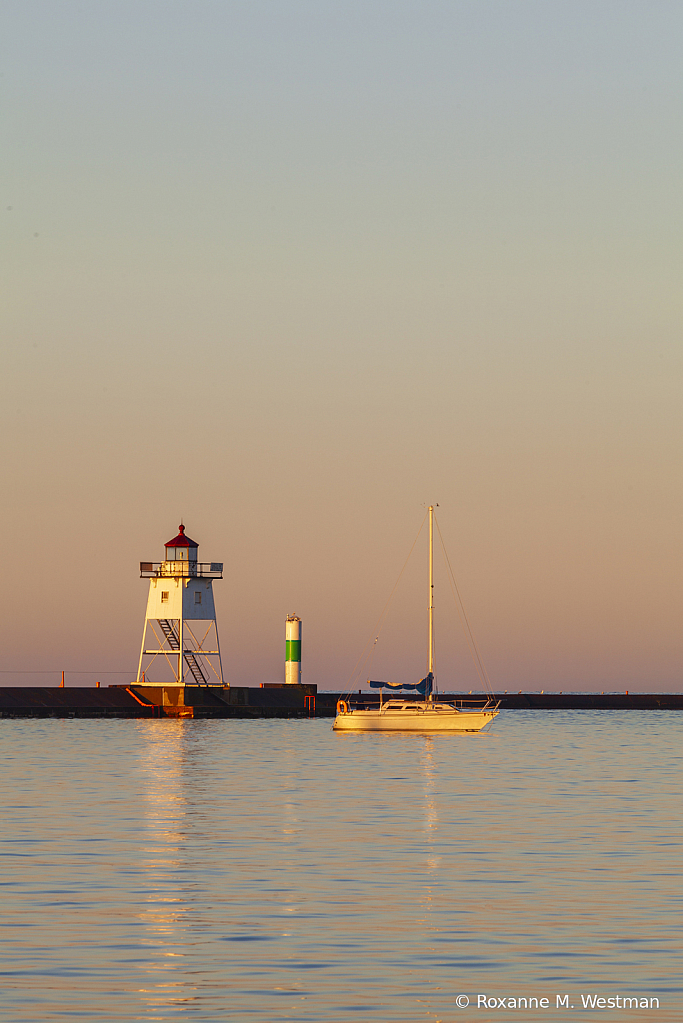 Early morning lighthouse and sailboat