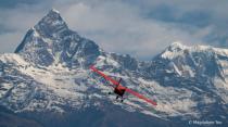 Red Plane at Himalayan Mountain Range