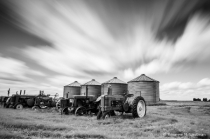Clouds passing by antique tractors