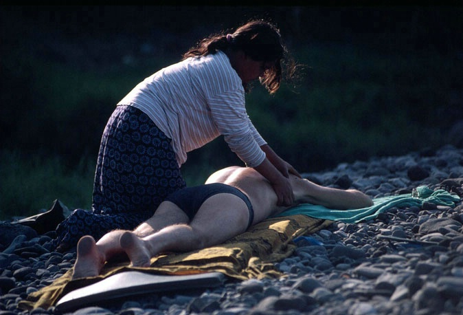 Balinese lady massages man on the stoney beach