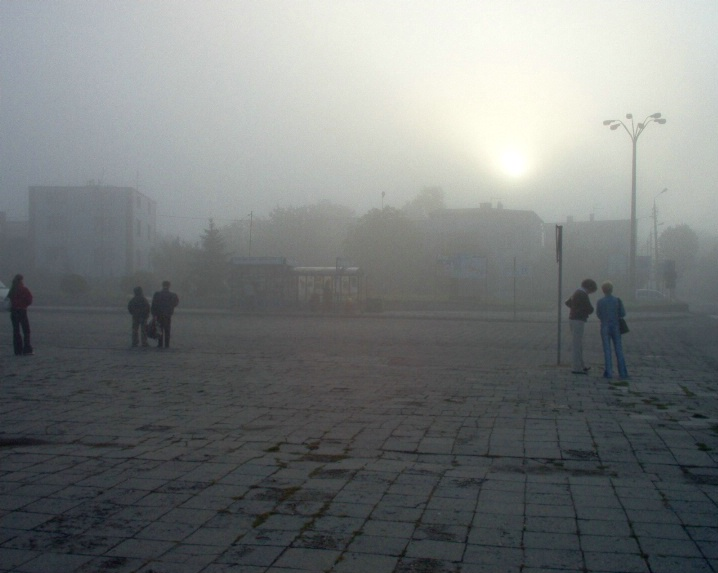 People waiting for a bus on a foggy day
