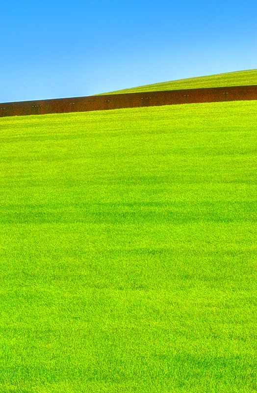 Blue Sky, Brown Wall and Grassy Knoll