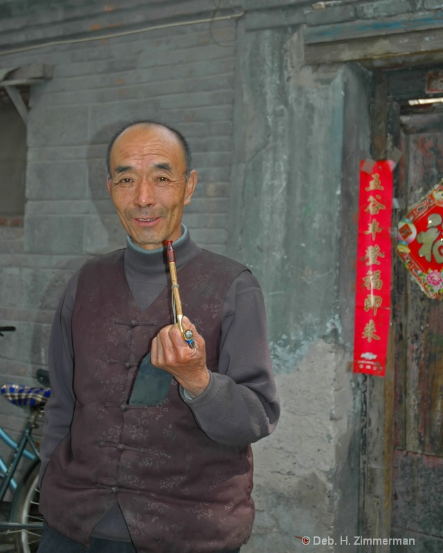 Chinese man and pipe in Beijing Hutong