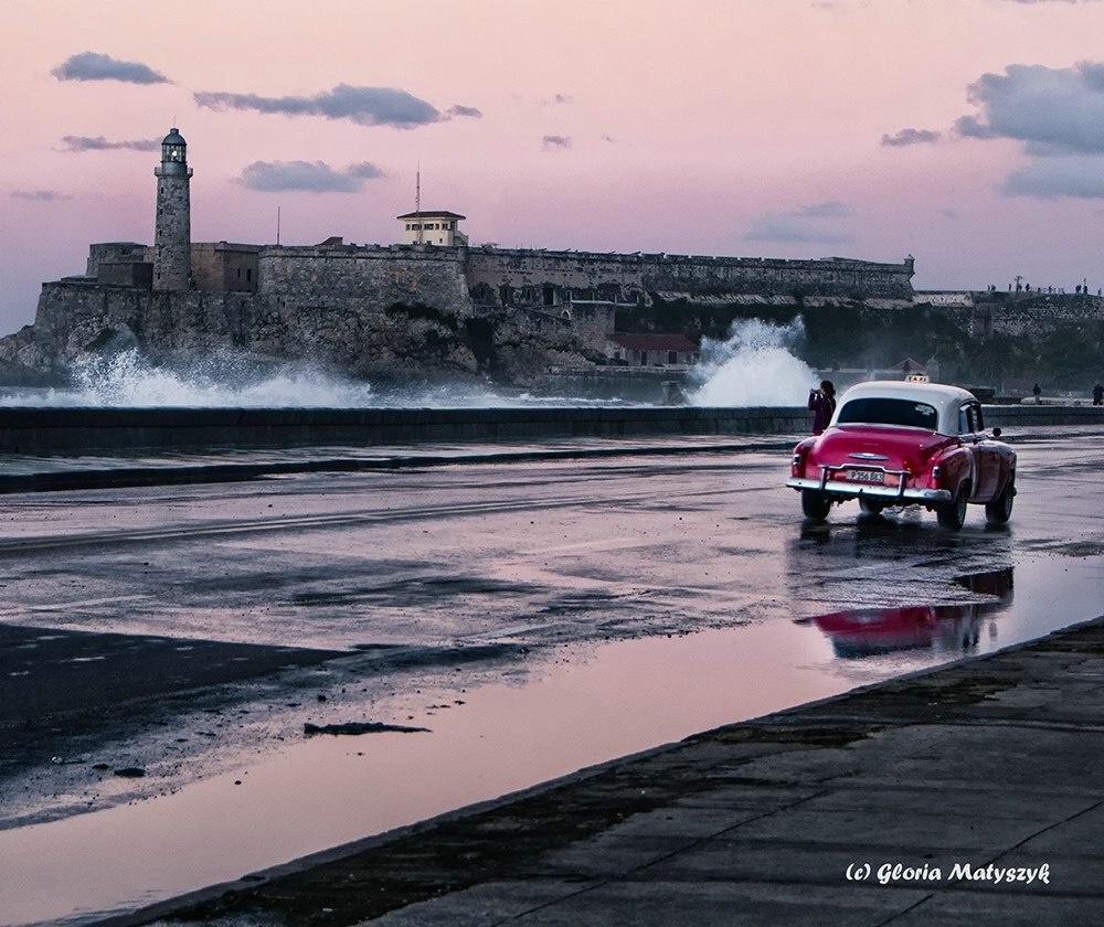 Waves and an old car at sunset in Havana, Cuba