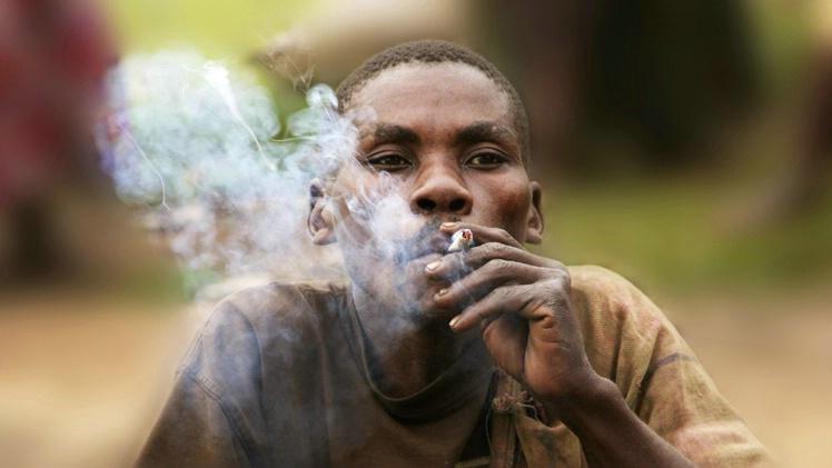 Smoke: Batwa Pygmy man outside Bwindi