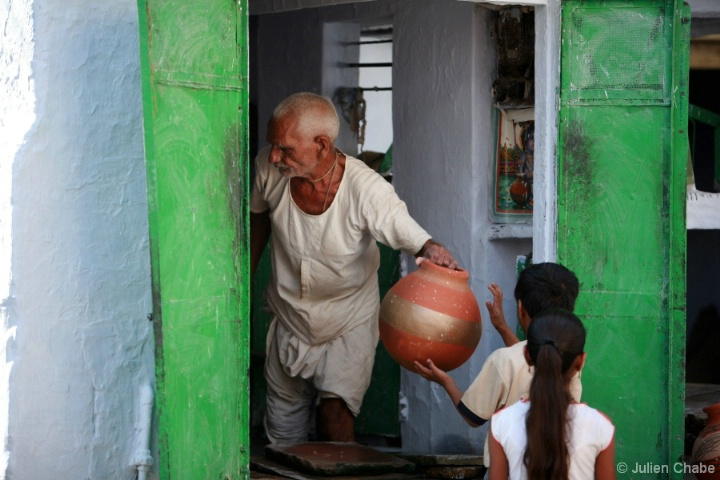 Old man giving water to kids