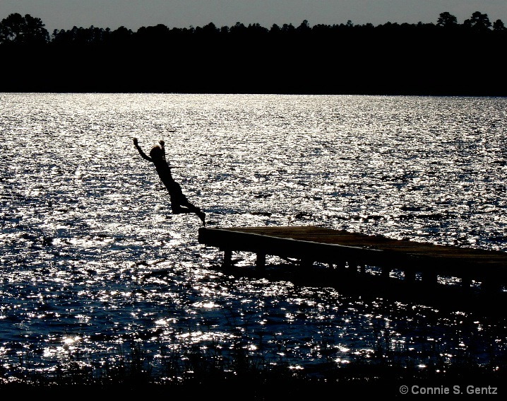 silhouette - jumping into lake