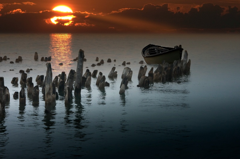 Sunset with boat and pilings