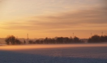 Freezing fog and snow on the fields at sunset