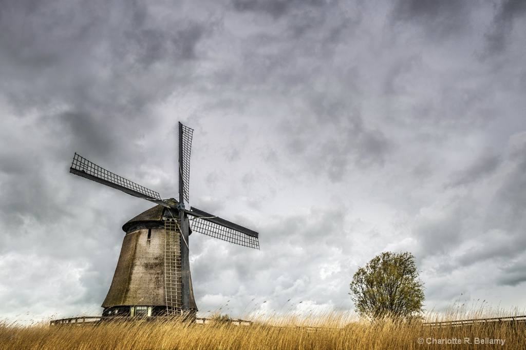 Traditional Dutch windmill against a stormy sky