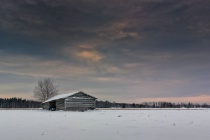 Snow Covered Barn House Under Dramatic Skies
