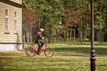 Park Worker Riding a Bike with a Rake