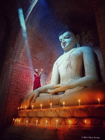 Novice monk praying with candle