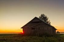 Midsummer Sunset Behind A Barn House