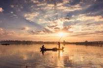 Fishermen under sunrise.