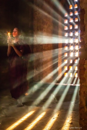 A novice praying with candle in Bagan